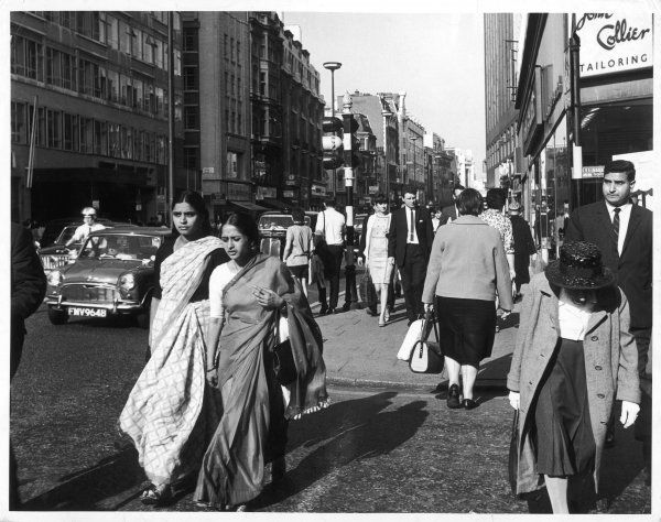 Two Asian women wearing traditional Indian saris and an Asian man, shopping in Oxford Street, central London
