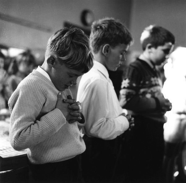 Children at Coughton Cope Infants' School bow their heads in morning prayer Date: 1973