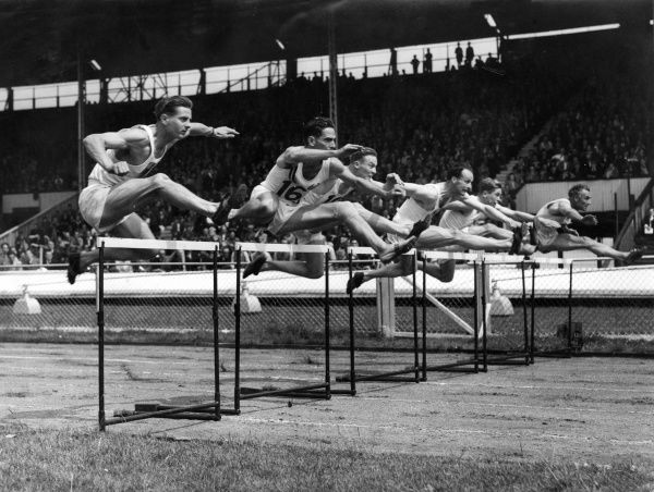 An athletics event with men taking part in a hurdles race.  circa 1940s