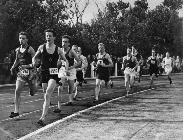 An athletics event with men running round a race track.  circa 1940s