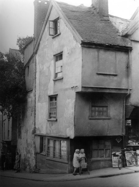 An atmospheric scene of an old house on a steep street corner in Exeter; two girls stand beneath the overhanging eaves while a young woman leans against the wall further down