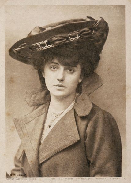 Miss Auriol Lee wears a coat with an unusual collar and a hat with a ribbon threaded through the brim perched at an angle on the top of her pompadour hairstyle