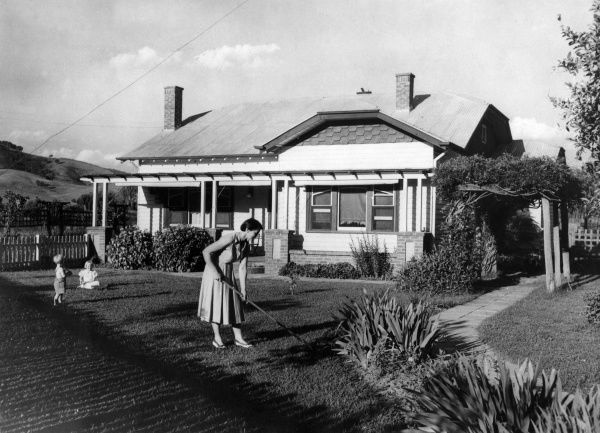 Mother rakes the lawn, while her happy children play together nearby at their new 'modern' detached house in north eastern Victoria, New South Wales, Australia. Date: 1950s