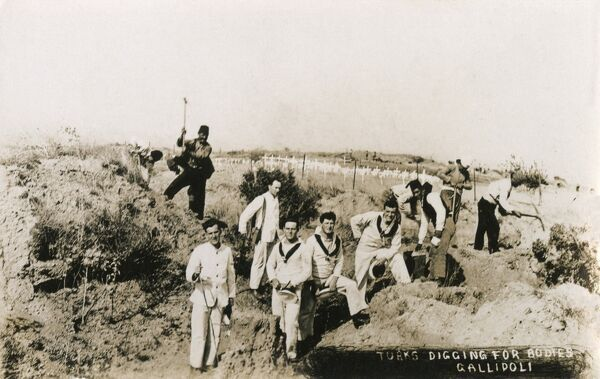 Australian Sailors visiting Gallipoli Sites - supervising Turks, put to the task of digging for bodies at Gallipoli - to be reinterred in the Allied Christian cemetery in the background