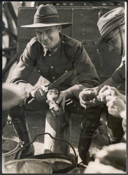 A cheerful Australian soldier peeling a potato (?) with a rather large knife