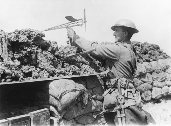 An Australian soldier in a front line trench at Croix du Bac, near Armentieres, northern France, during the First World War. He is using a wind direction indicator as an anti-gas precaution. Date: 18 May 1916