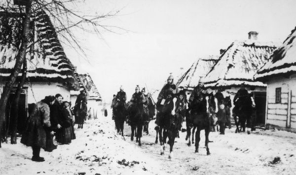 Austrian cavalry advance through a Polish settlement on the Eastern Front