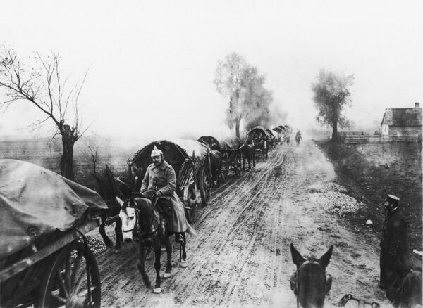 Austrian troops, some on horseback, some in covered wagons, advance along a muddy road on the Eastern Front