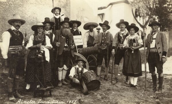 Austrian Village Ensemble, featuring, yokels, musicians and a variety of age groups! The caption reads 'Aineter Militia'. Date: 1928