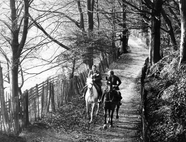 A young couple on a romantic autumn horse ride in the English countryside. Date: 1930s