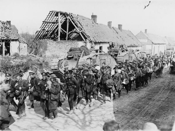 British infantry going back through Aveluy, passing tanks of the Second Battalion on the Western Front in France during World War I in 1918