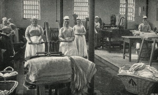Interior of laundry at Aylesbury prison. Uniformed women handle the washing on trolleys and in baskets which bear the convict arrow insignia. Date: circa 1900