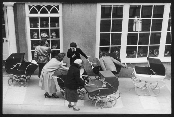 Five young mothers comparing babies in their prams during the post World War Two Baby Boom, which lasted from approximately 1946-1964