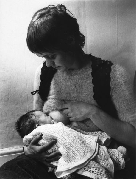 A tiny baby being breastfed. Date: circa 1960