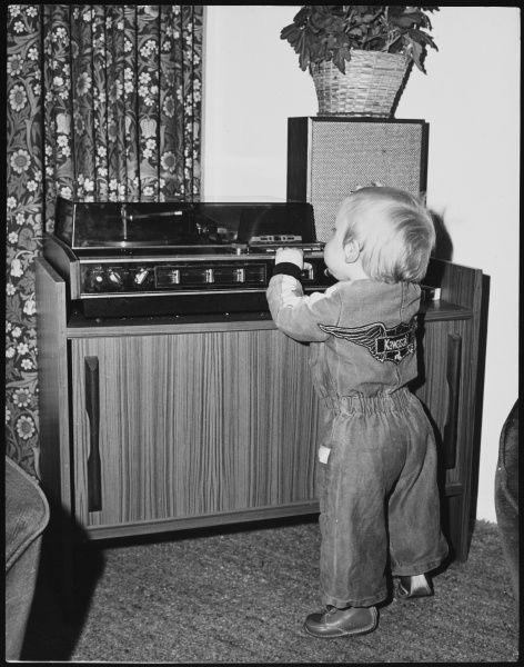 A baby boy fiddling with a stereo radiogram - naughty!