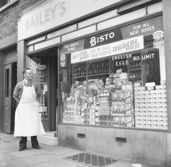 Bailey's Grocery Store and the proud shopkeeper, assessing the weeks window display. Photograph by Norman Synge Waller Budd
