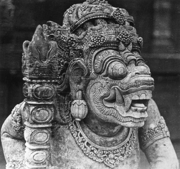 The carved head of a Hindu temple figure at Bali, Indonesia. Date: 1930s