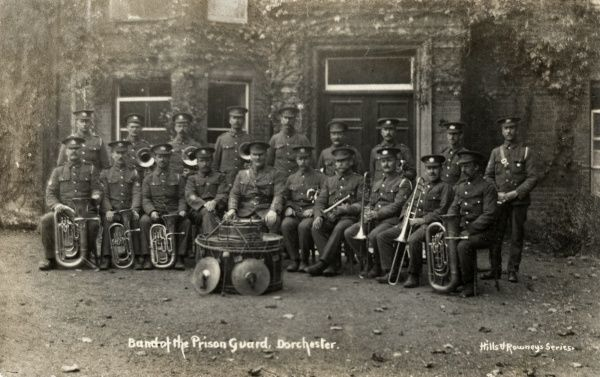The officers' wind band at Dorchester prison. The members in their uniforms pose with their instruments. Date: Date unknown