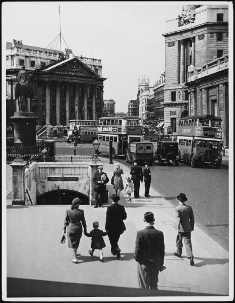 Busy scene near the Bank of England, with many well- dressed men in suits and hats and a couple and their son hand-in-hand approaching Bank underground station
