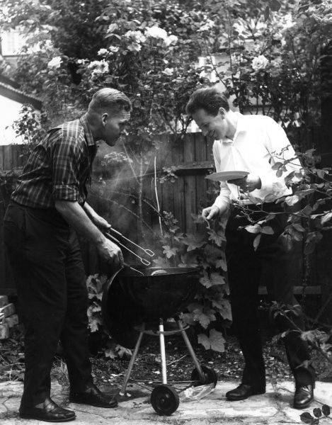 A kind man offers his neighbour the last sausage from his trendy tripod barbecue! Date: late 1960s