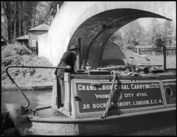An old man steers his barge under a bridge on the River Gade, near Watford, England, part of the Grand Union Canal