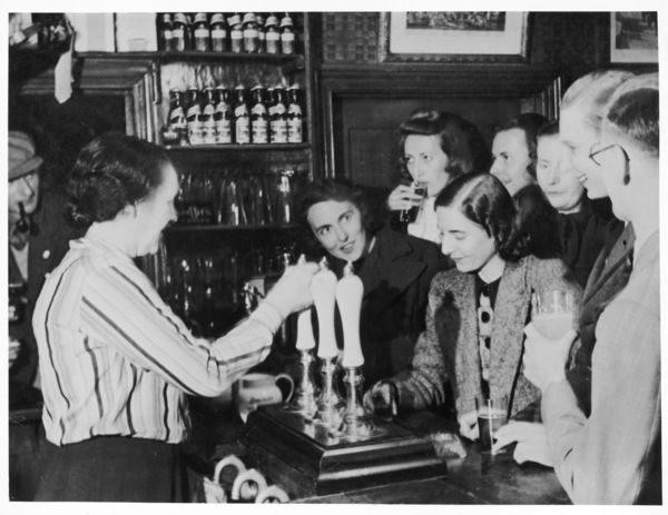 A barmaid pulls drinks for a jolly group of mostly young women