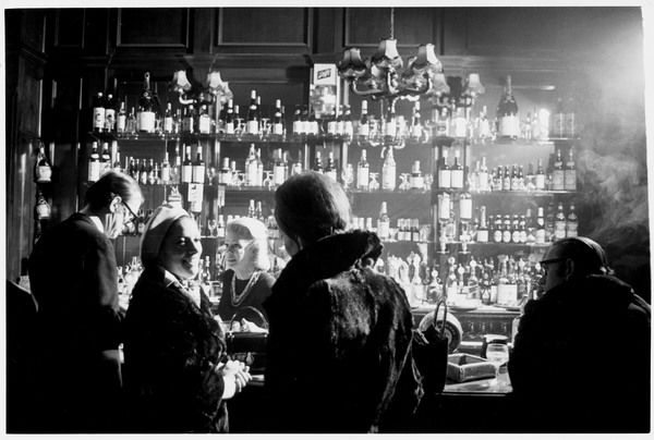 A barmaid serves a customer in a smokey London pub. On the back wall is a fine selection of spirits while in the foreground, punters chat among themselves
