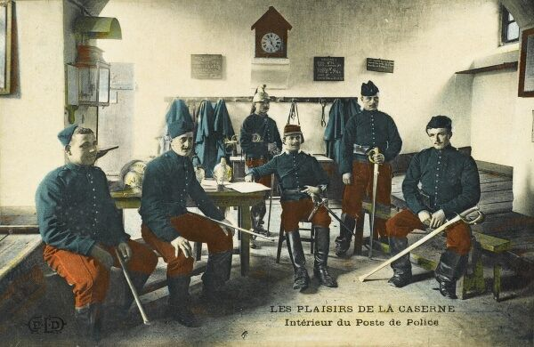 The interior of a Police barrack room, with a group of French soldiers (some seated) in the foreground, all bearing swords, engaged in police duty