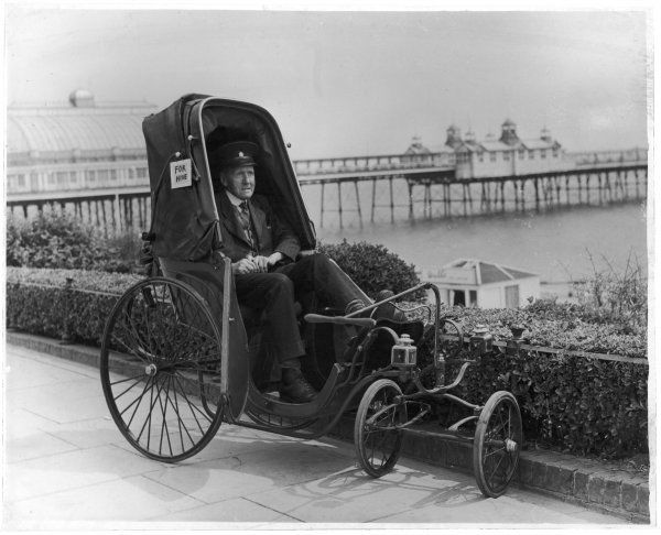 An attendant with a bath chair 'for hire' waits for a customer whom he will pull along the sea front at Eastbourne