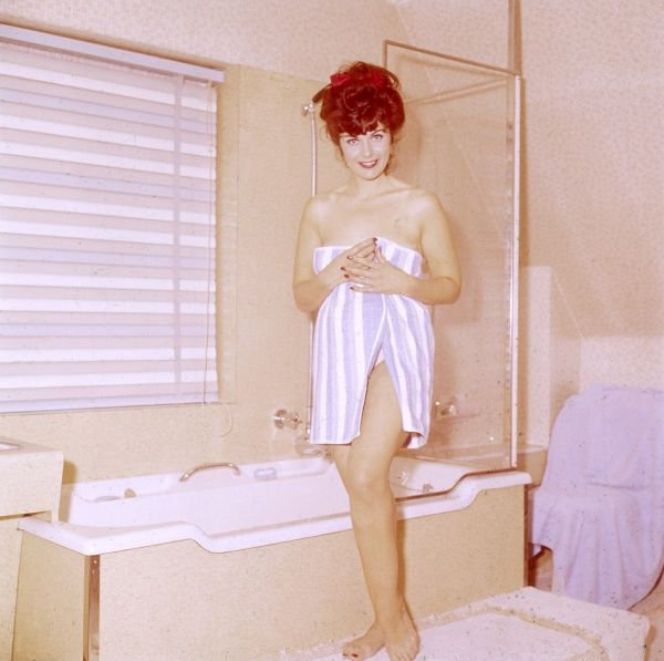A cute model getting out of the bath, wearing only a small towel! Date: 1966