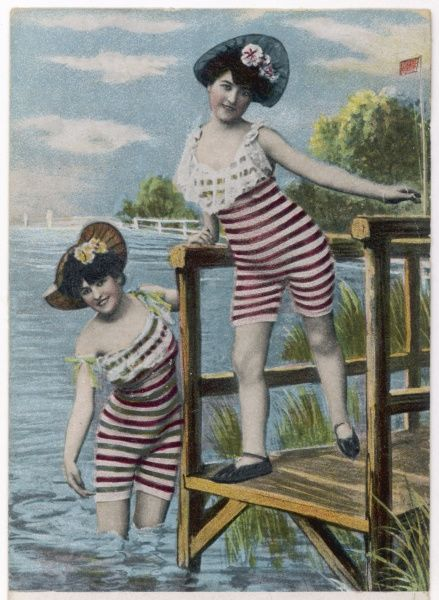 Two bathing beauties in red and white stripy costumes and hats, on a jetty