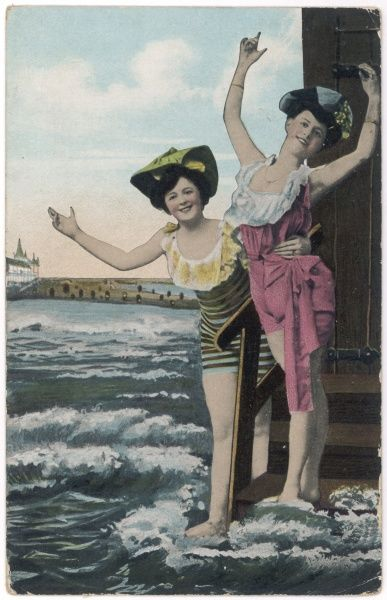 Two bathers in fancy swimsuits and hats pose theatrically on the steps of their bathing hut