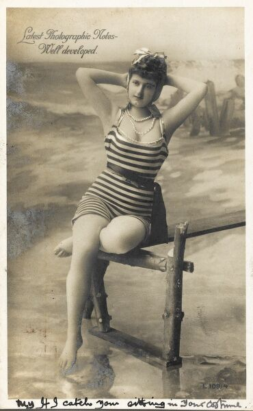 Latest Photographic Notes: Well Developed - a fine photographic postcard of a fetching young lady in her best pearls and favourite stripey bathing costume, perching delicately on the end of the quay, her toes barely touching the water