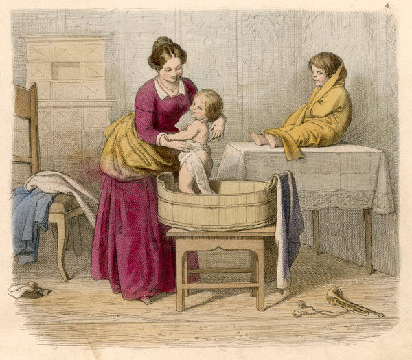 A mother bathes her two children: the elder, a toddler, sits drying on a table, while baby stands in the bath tub