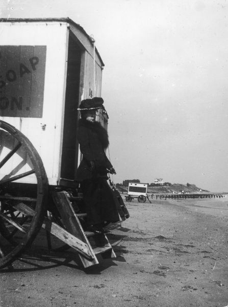 A rather formidable looking lady stands on the steps of a bathing machine at Walton-on- the-Naze, Essex, England, probably wondering if it's to chilly for a dip in the sea