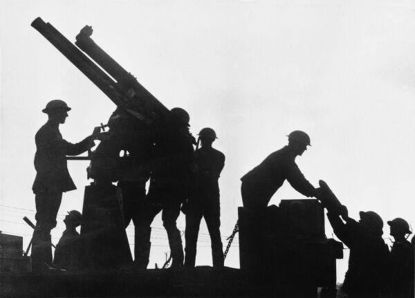Silhouette of an anti aircraft gun (13 pounder 9 cwt) mounted on a motor lorry being fired by soldiers at the Battle of Broodseinde on 4th October 1917 during World War I