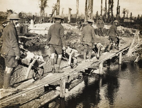 Battle for Broodseynde on the British Western Front in 1917. Soldiers of an English county regiment cross a temporary bridge with stones in wheelbarrows for road making