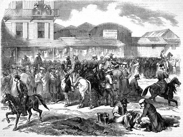 Engraving of busy street scene at Balaklava at the end of the Crimean war. Soldiers and civilians jostle together, some on horseback, civilians in typical russian dress, caps and belted long coats. In the background one can see the wooden buildings