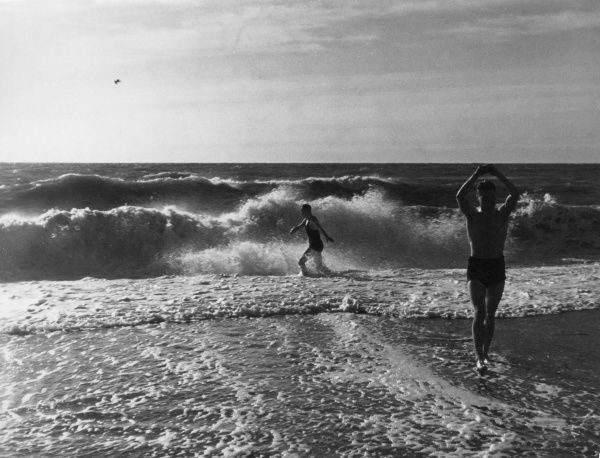 A young man does his exercises on the beach while his girlfriend plays in the surf behind him. Date: 1930s