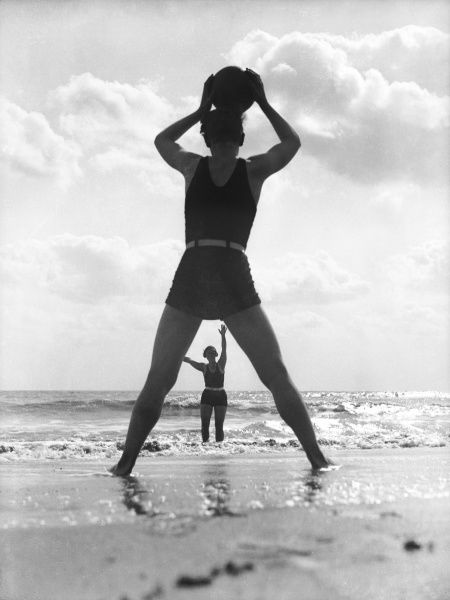 A young couple throwing a ball to one another on the beach at Cliftonville, England