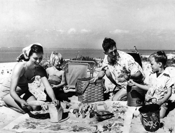 Father offers his son some fruit, while mother dishes up some popcorn at this family beach picnic. Date: 1960s
