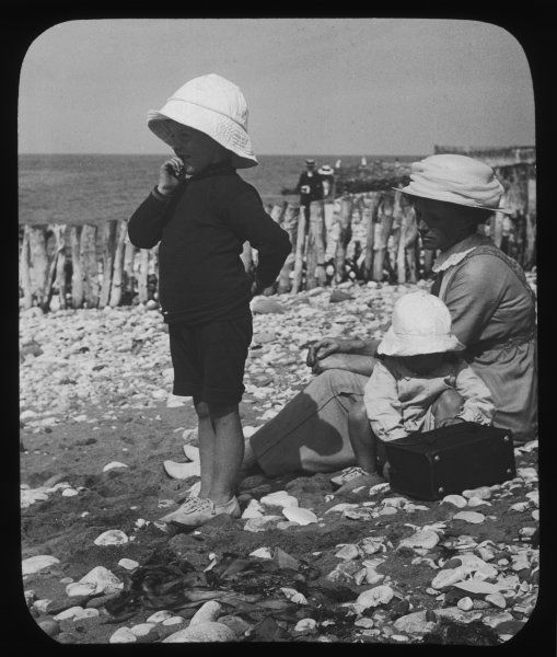 A pensive young mother and her two children, all wearing hats, relaxing together on a beach among the pebbles and seashells. The little boy looks out to sea