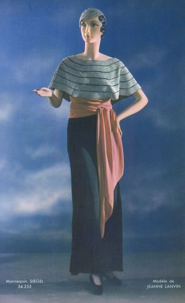 A gown by Jeanne Lanvin with a black narrow skirt and beaded cape collar worn with a matching beaded hat. A long pink scarf is worn round the waist