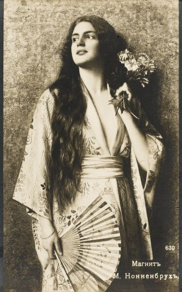 Beautiful Russian Actress with extraordinary long dark hair and holding a small posy of flowers