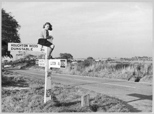 A girl in sturdy shoes and long socks, probably school uniform, perches on top of a signpost by the B579 road near Chalton in Bedfordshire