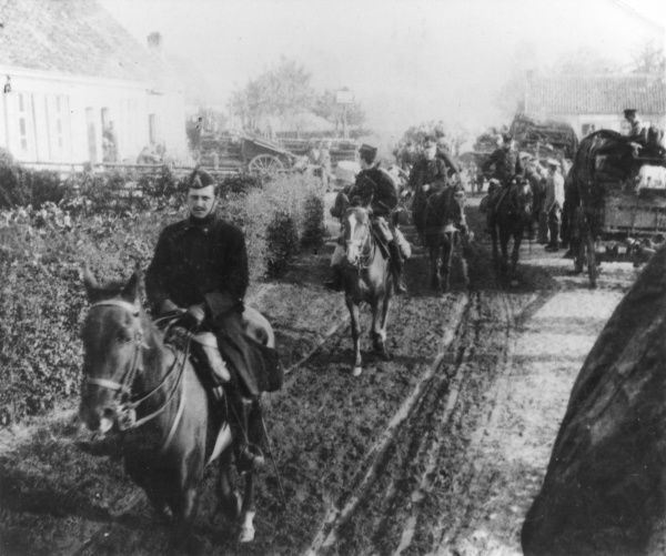 Belgian cavalry passing through Sommergem (Somerghem), East Flanders, Belgium, during the First World War. Transport of the 2nd Scots Guards can be seen on the right, having halted during the march from Bruges to Ostend. Date: 8 October 1914