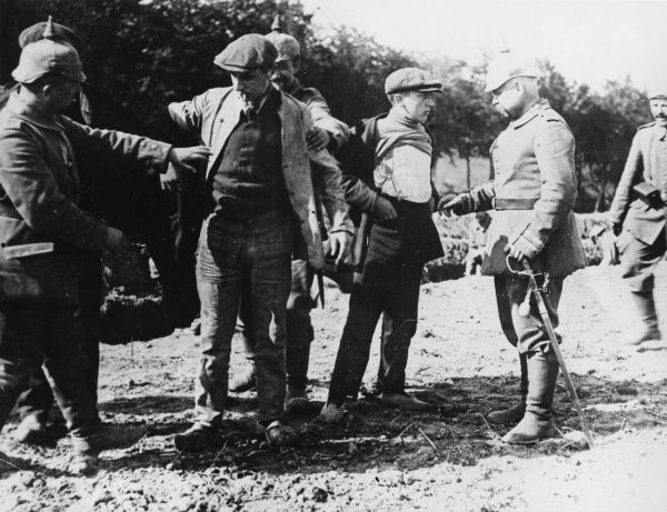 Belgian civilians being subjected to a vigorous search by German soldiers on the Western Front during World War I