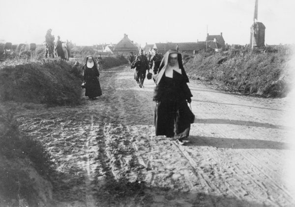 Belgian nuns and others walking along a road at Adinkerke, behind the Yser front in Belgium, during the First World War. Date: 1917