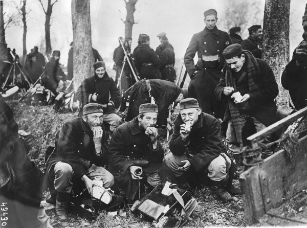 Belgian soldiers eating their dinner in the open air in northern France during the First World War. Date: 1914-1918