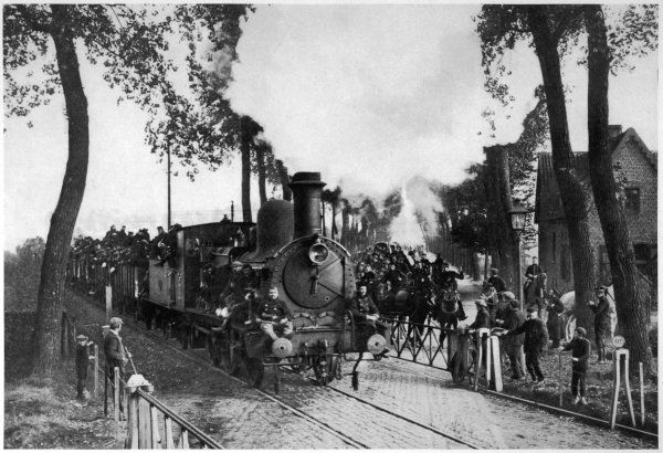 The Belgian Army is forced to evacuate Antwerp, overwhelmed by the German advance : at Maldeghem, near Bruges, a train carrying infantry crosses a column of cavalry